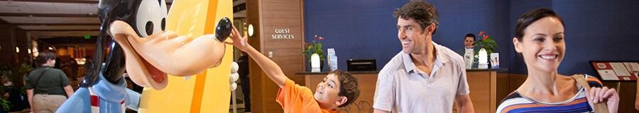 Un niño toca la estatua de Goofy surfista cuando él y sus padres pasan por el lobby del hotel
