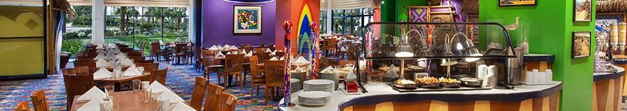 Una mesa del servicio bufet y las mesas del comedor puestas y listas para recibir a los Huéspedes en un restaurante inspirado en el surf