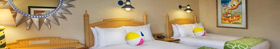 Una cama Queen Size con una almohada en forma de pelota de playa, un escritorio, además de un sillón y una ventana
