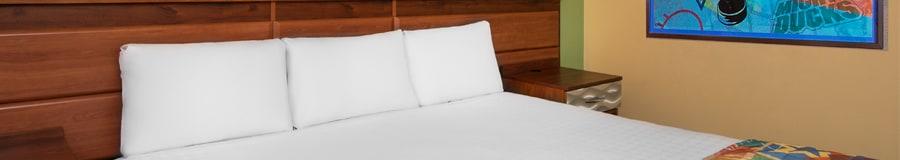 Almohadas cubren la cabecera de una cama grande y un póster de