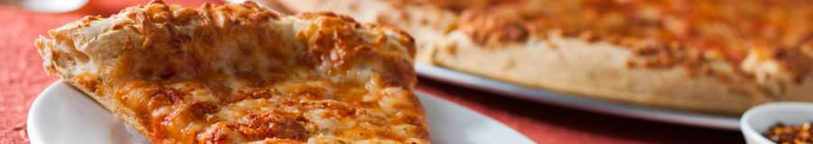 A cheese pizza with crunchy crust, plated directly from an oven pan, next to toppings and a tall drink