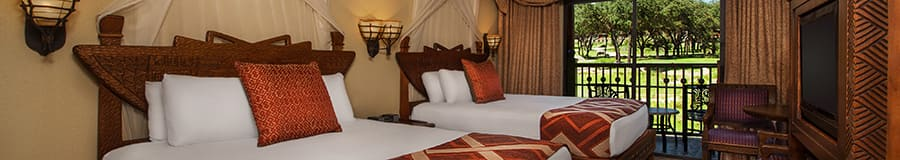 2 camas Queen Size junto a un balcón con vista a la sabana