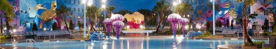 Uma vista noturna da piscina de Procurando Nemo no Disney's Art of Animation Resort com áreas de diversão coloridas