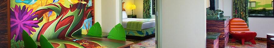 Uma cama queen com uma cabeceira colorida com Zazu de O Rei Leão da Disney em frente a uma TV de tela plana em uma cômoda com temática da selva