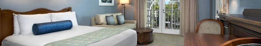 Una habitación con un sofá, una lámpara, una silla, una cómoda, cortinas y acceso al balcón