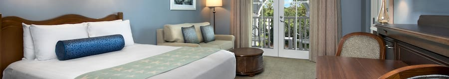 A room with a couch, a lamp, a chair, a chest, curtains and balcony access