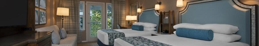 Deux grands lits, un bureau, Commode avec TV, canapé-lit et, au-delà, un balcon