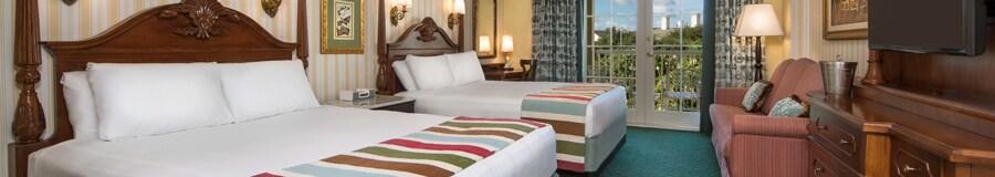 Dos camas Queen Size con cabeceras, un TV, una cómoda, un sofá cama y, más allá, un balcón
