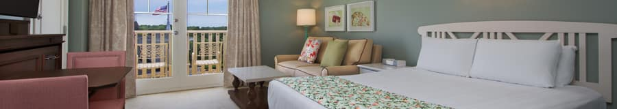 A queen bed and, beyond, a nightstand and a double sleeper sofa and a coffee table