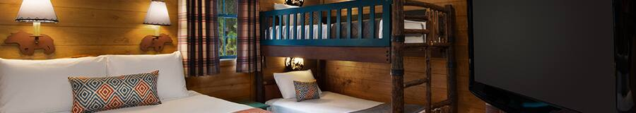 A flat screen TV, a queen size bed, 2 decorative sconces and a set of bunk beds