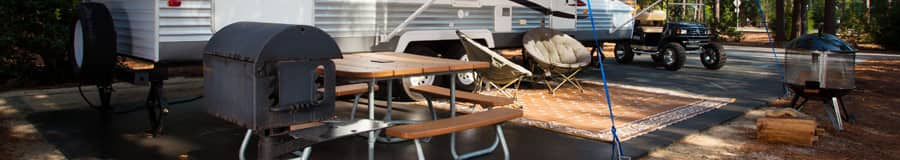 Una mesa de picnic junto a una parrilla y una casa rodante