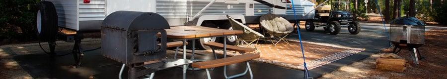 Mesa de piquenique ao lado de uma churrasqueira e um trailer