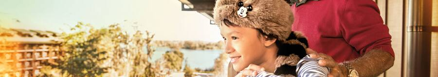 A young boy wearing a novelty coonskin hat takes in views from their room's balcony with his father