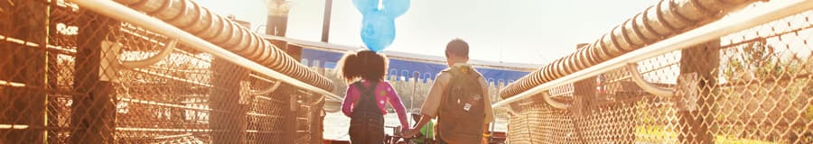 A young sister with a Mickey ears balloon holds her brother's hand while crossing a bridge