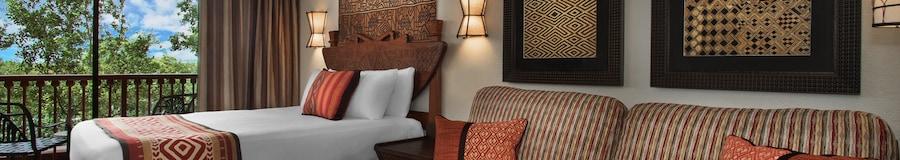 Un sofá, almohadas decorativas, 3cuadros, 2 lámparas de pared, una cama y un balcón con vista a una exuberante sabana