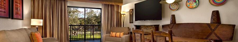 Un espacio con temática africana, con un sofá, mesa ratona, silla y mesa de restaurante, más vista de animales