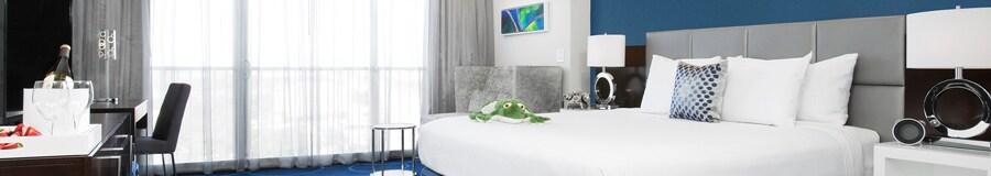 """Uma sala com cadeiras, uma escrivaninha, 2mesas de apoio, uma TV, uma cama com uma pelúcia de """"The Princess and the Frog"""", 2luminárias e quadros"""