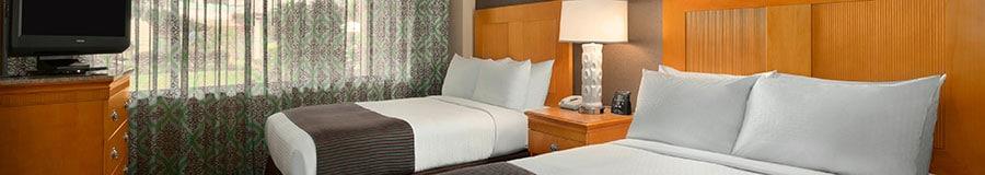 Um quarto com 2 camas, uma TV, uma janela e uma mesa de cabeceira com uma luminária