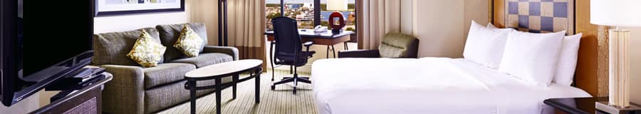 Una habitación con una cama, 2lámparas, 2 sillas, un TV, un sofá, 2 mesas y cajones
