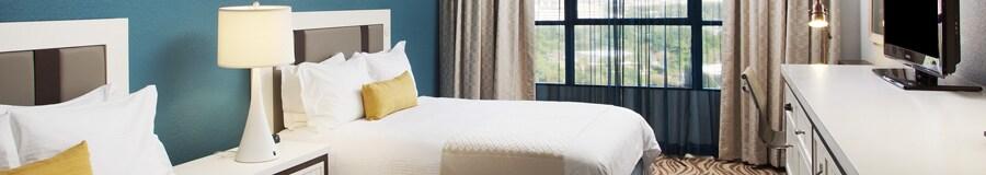 Una habitación con 2camas, 2lámparas, un espejo, un TV, una silla y cortinas