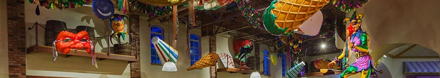 Mardi Gras masks and a series of parade displays hanging down from the rafters of a high ceiling