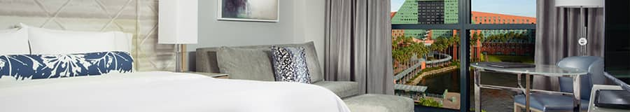 King sized bed next to night table and lamp with sofa and ottoman in the background