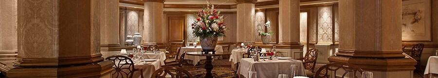 Comedor formal en Victoria & Albert's, con mesas con buqué de flores y porcelana fina
