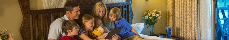 Uma família de 6 pessoas, sentada em uma cama, usa um tablet para planejar seu dia