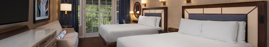 Une chambre avec 2lits, tiroirs, un canapé, une TV, un tableau, lampes, un miroir, des rideaux et l'accès à un balcon