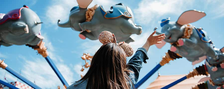 A young woman wearing Mickey ears waving a hand in front of the Dumbo the Flying Elephant attraction