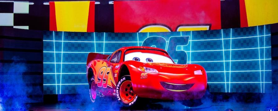 Lightning McQueen, no palco em frente a um grande público, com seu número de corrida em destaque acima