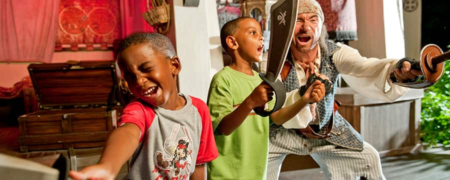 A pirate teaches 2 young Guests how to snarl and sword fight