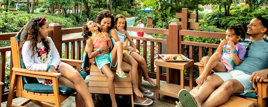 A smiling family enjoys a fruit plate while sitting on wooden chairs on a porch