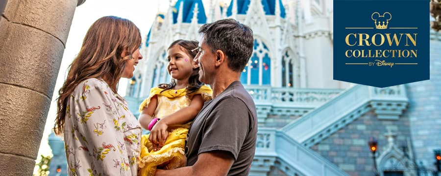 A young couple smiling with their small daughter in front of Cinderella Castle