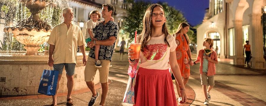 A smiling girl with a shopping bag walks through Disney Springs
