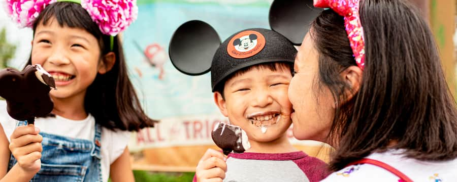 A mom and her two children enjoy Mickey ice cream bars