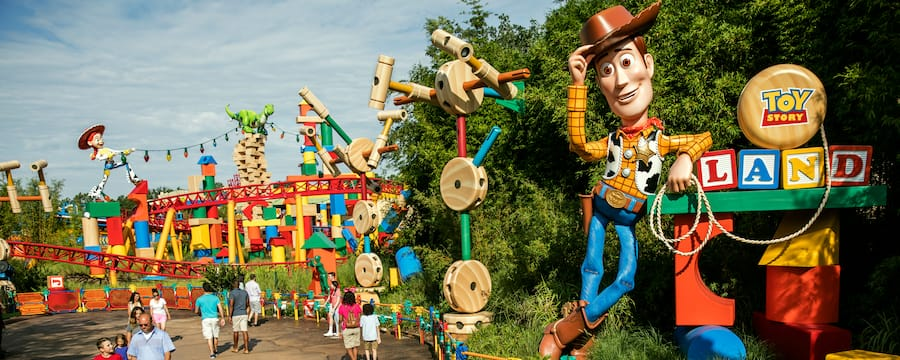 The entrance to Toy Story Land featuring guests entering the near a giant Woody