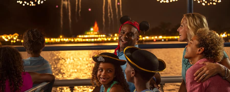 A family, wearing pirate themed Mickey Ears, experiences Pirates & Pals Fireworks Dessert Voyage
