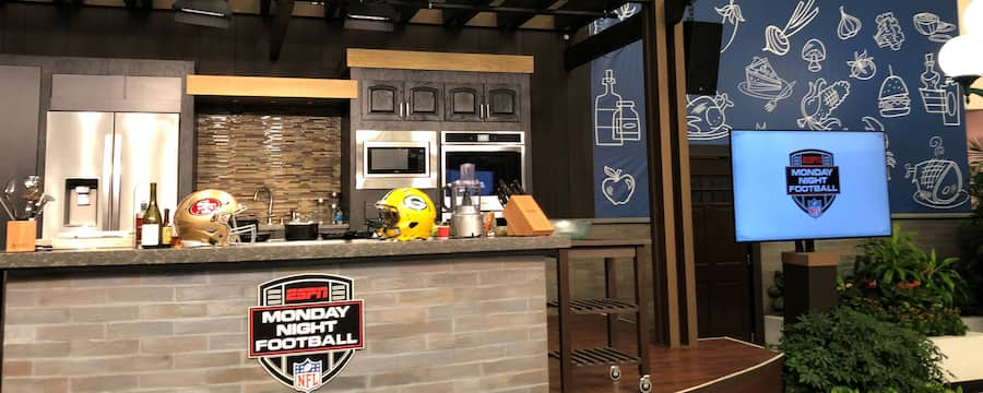 San Francisco 49ers and Greenbay Packers football helmets on a kitchen counter next to a bottle of wine