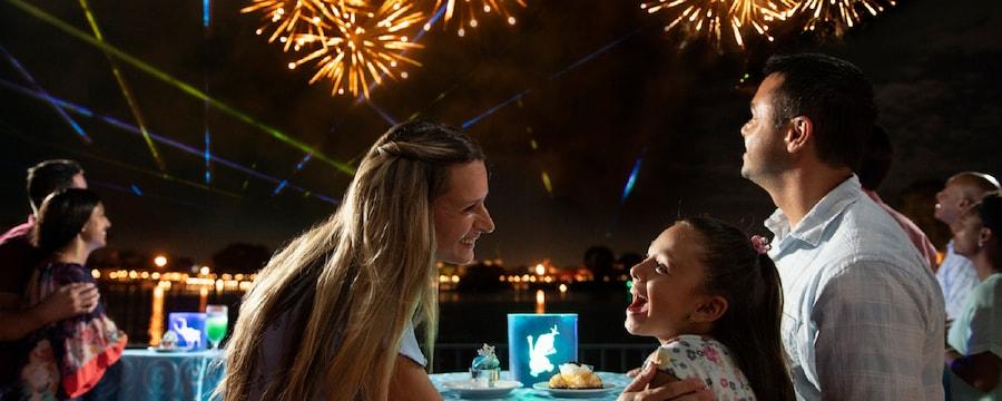 Una familia observa los fuegos artificiales mientras comen postres