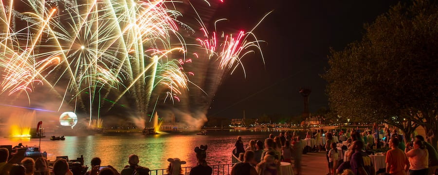 A crowd gathered around the edge of a lagoon watching a light and fireworks show