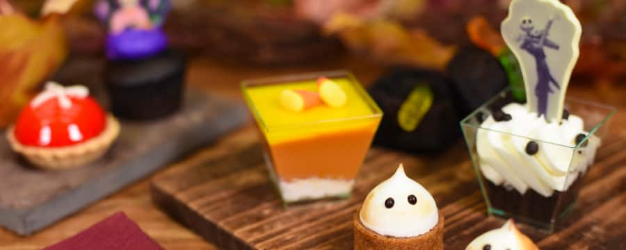 Several wooden slates holding small Halloween theme desserts on a spoon resting on a napkin