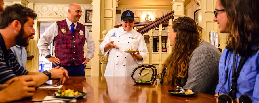 A VIP Tour Guide watches as a chef presents a sample dish to Guests at a dining table