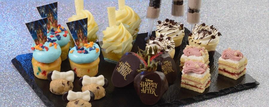 Un plateau de desserts avec des petits gâteaux miniatures, des gâteaux au fromage miniatures, des carrés de gâteau miniatures, des coupes de mousse, des fraises trempées dans le chocolat, des gâteaux-sucettes avec des Mickey en chocolat et des bouchées de pâte à biscuits avec des oreilles de Minnie.