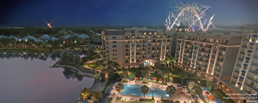 A large hotel courtyard featuring a pool with many lawn chairs and fireworks in the background