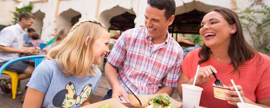 Un hombre, una mujer y su hija sonríen mientras comen en una mesa al aire libre