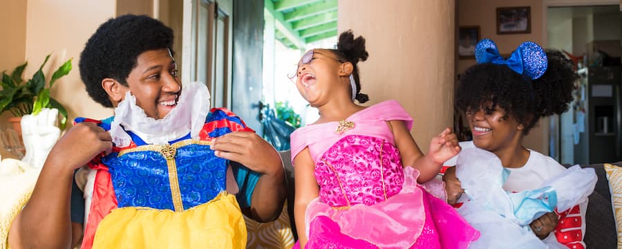 Family of 3 with Disney princess costumes in hand