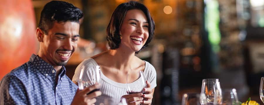 A man and a woman laugh while drinking wine in a restaurant