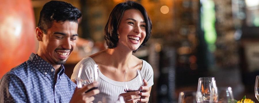 Um homem e uma mulher sorriem enquanto bebem vinho em um restaurante