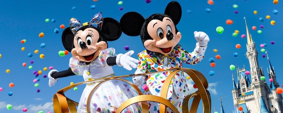 Confeti volando alrededor de Mickey Mouse y Minnie, con atuendos festivos con un diseño de confeti